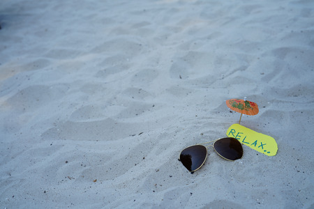 sunglasses with relax message on yellow paper and umbrella on beach background for retire or retirement plan concept Archivio Fotografico