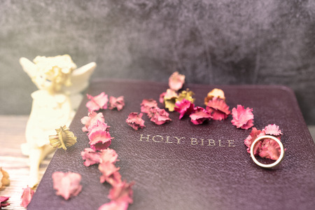 angle doll and dry flower with gold ring in holy bible book in the gold llights for background and inspiration 스톡 콘텐츠