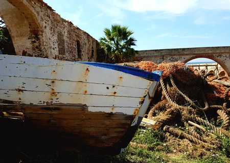 An old wooden fishing boat sits abandoned
