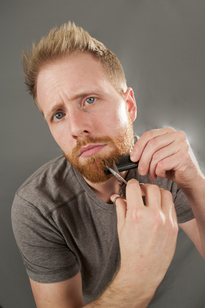 comb: Man Trimming beard with scissors and comb