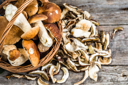 Fresh boletus mushrooms in a basket and dry mushrooms on wooden table, overhead Imagens