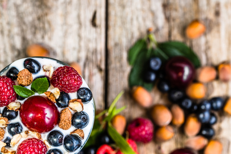 summer fruits: Yogurt ice cream with berry fruits and hazelnuts in a glass cup, frozen dessert, summer healthy eating concept, view from above