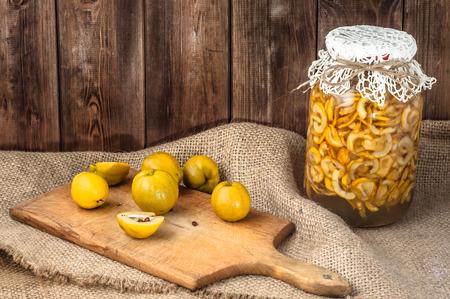 membrillo: Frasco de tintura con frutas de membrillo en una mesa de madera cubierta con tela de saco.