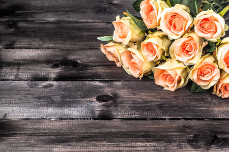 Valentines roses on rustic wood background. Flowers backgrounds.