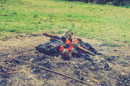 Rustic bonfire outdoors, vintage photo.
