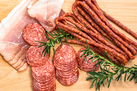 carnes: Assortment of meats: kabanos, salami prosciutto slices on wooden board.