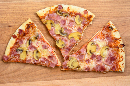 fungi: Pieces of pizza on wooden board. Stock Photo