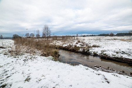 thawed: Landscape of fields by the river during thaws at early spring or late winter.