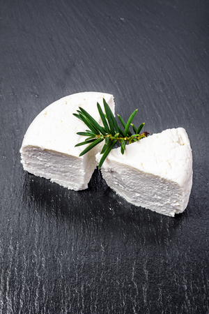 White cheese or feta cheese isolated on black background.
