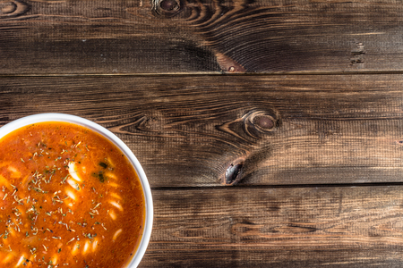 a portion: Cooked tomato soup with noodles on a wooden table, serving size in a bowl, top view, copy space