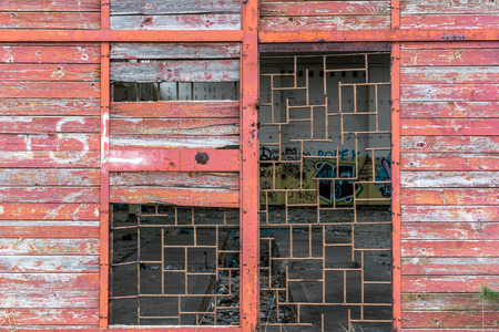 window graffiti: Old industrial factory entrance with damaged wooden door of abandoned industry Stock Photo