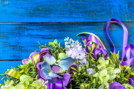 Easter wreath with decoration, easter eggs and flowers on wooden background Stock Photo