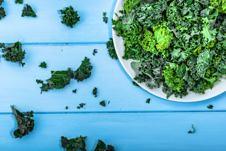 cutted: Green vegetable, leaves of kale from above on white plate, vegetarian food concept