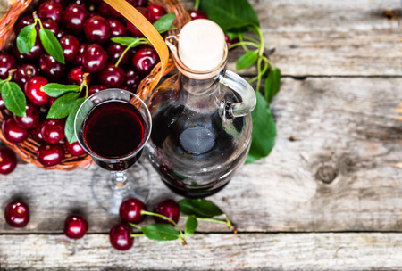 Glass of alcohol tincture made from cherry fruits, liquor in a bottle on rustic background