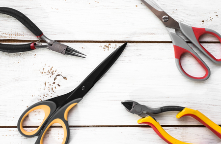 pincers: Pincers and scissors tools on wood background Stock Photo