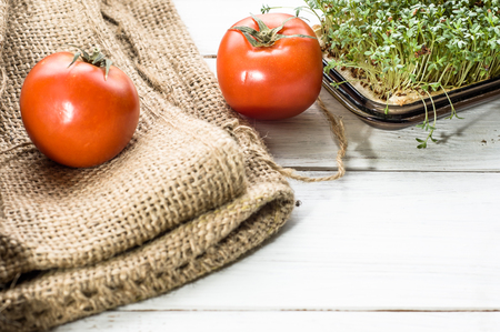 Cress and tomatoes on wooden background, healthy eating, vegetarian diet concept