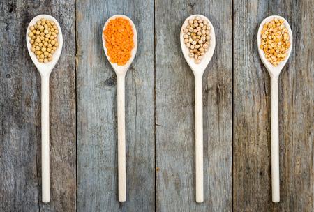 garbanzos: Concepto de comer sano. Dieta para los ingredientes vegetarianos y veganos: alimentos para semillas y habas de soja, las lentejas, garbanzos y guisantes de cucharas de madera
