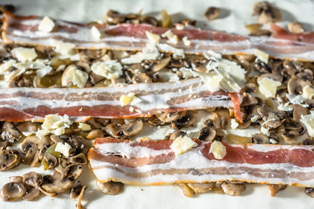 pasteleria francesa: Raw dough with mushroom and bacon stuffing. Preparing french pastry snacks Foto de archivo