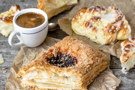 pasteleria francesa: Engorde desayuno alimentos - pastelería francés, pan de dulce y la taza de café en la mesa de madera Foto de archivo