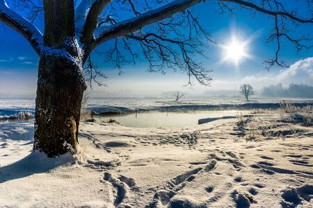 covered fields: Winter river landscape, moody scenery with morning sun on blue sky