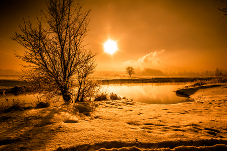 covered fields: Winter river landscape, moody scenery with morning sun reflection in the water Stock Photo