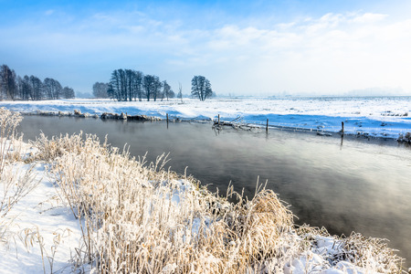 snowy field: River in winter landscape, snow and blue sky Stock Photo