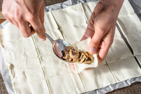 stuffing: Filling dough with a mushrooms stuffing, preparing puff pastry rolls