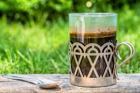 Glass coffee cup in the morning garden on blurred grass background, vintage style metal handle