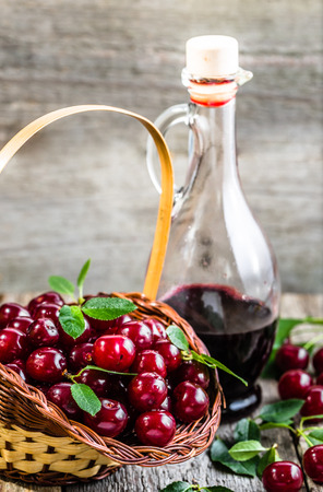Cherry wine in a glass bottle on wooden table. Sweet alcohol made from cherry fruits