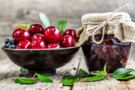 preserves: Cherry jam in jar and fresh cherries in a bowl, homemade preserves on rustic background
