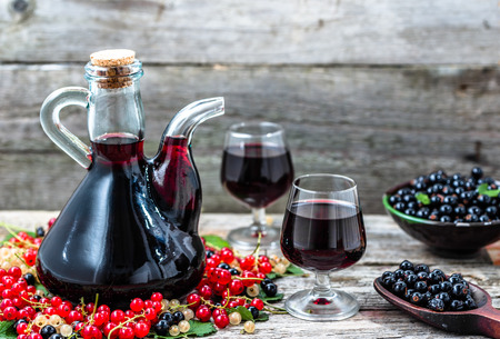 Old wine carafe on wooden table. Sweet alcohol made from fruits many variety berries currant