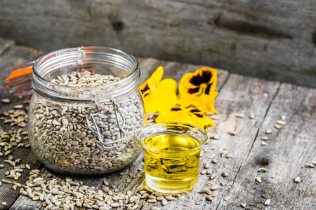 measuring cup: Glass of oil from sunflower seeds, vegan food background