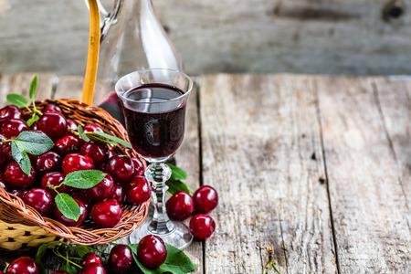 木製テーブルの上のガラス瓶のワイン桜。桜の果実から作られた甘いアルコール 写真素材