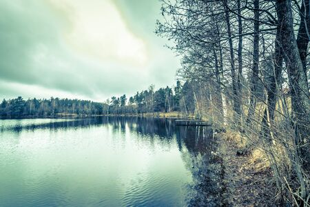 Lake landscape with forest romantic scenery over calm water surface, vintage photo Stock Photo