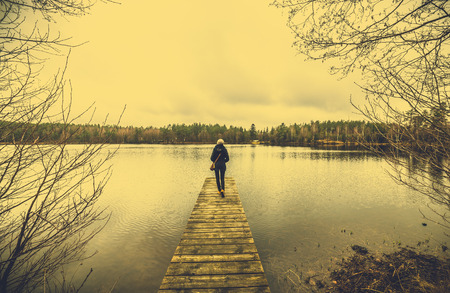 Boho woman on wooden pier over lake, landscape with moody sky