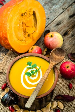 butternut: Pumpkin soup with cream and parsley, healthy food cooking concept Stock Photo