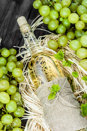 White wine bottle from green grape. Homemade wine in aged wooden pantry. Stock Photo