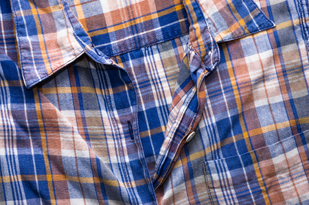 Textile texture of the checkered shirt, closeup the fastener useful as background