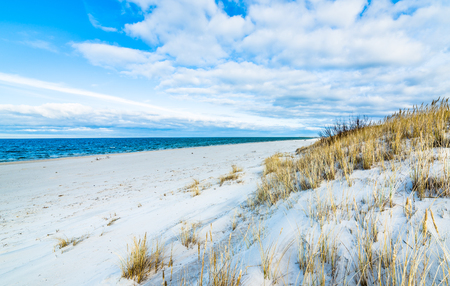 Sea beach landscape and blue sky. Sand dune with grass, Leba, Baltic Sea, Poland Stock Photo