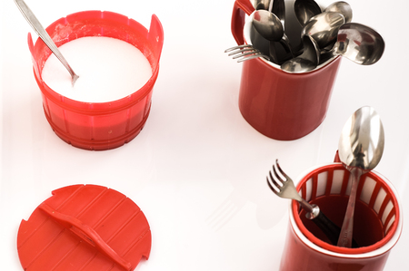 Salt shaker and kitchen utensils in red cup on a white background