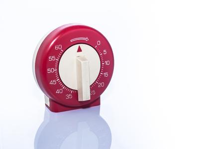 timekeeping: Red, vintage kitchen timer on white background