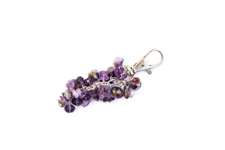 Keychain made with silver color metal, violet stones and crystals isolated on white background