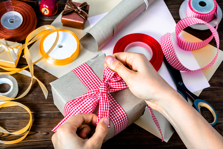 Wrapping christmas present with gray paper and ribbons. Hands making bow on gift.