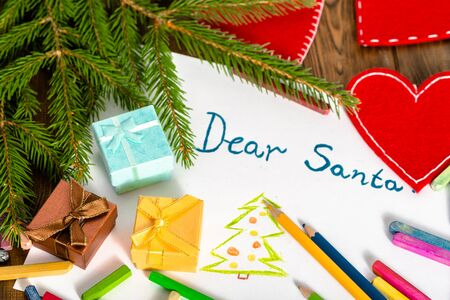 Traditional Christmas letter to Santa Claus with presents and green Christmas tree branch, Dear Santa greeting card written by hand by kid.