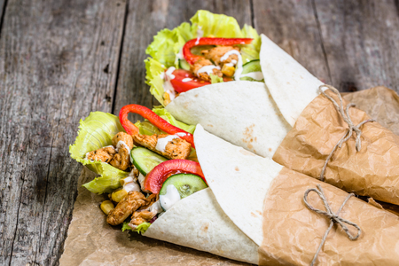 Mexican fajitas, tortilla wraps filled with fresh vegetables and grilled chicken on rustic wooden table