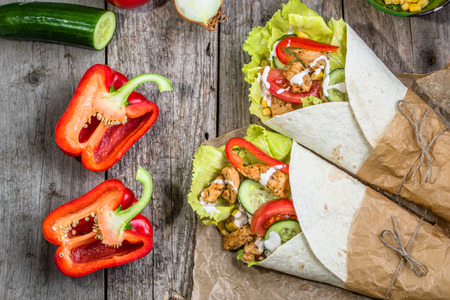 Delicious tortilla wraps, burritos  sandwiches filled with chicken meat and vegetables, fast food of mexican cuisine Stock Photo