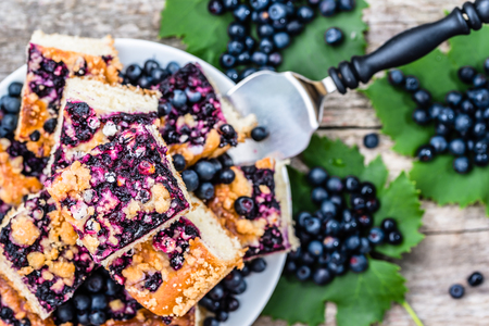 Sweet pastry with blueberry fruits on yeast cake, pieces on plate, summer baking concept, overhead
