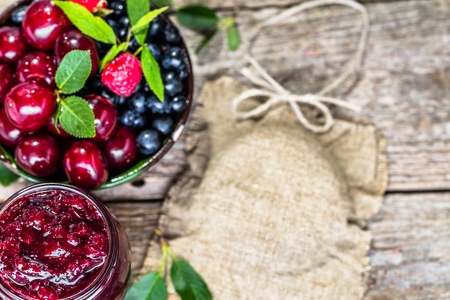 Homemade cherry jam and fresh cherries in a bowl on rustic background Banco de Imagens - 81072372