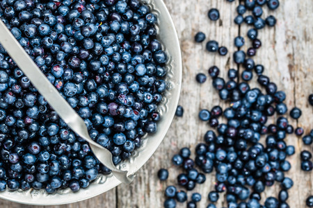 Fresh bilberries in basket on wooden table, ripe fruits from forest on farmer market from above Stock Photo