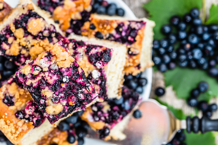 Sweet cake pieces with fruits of blueberry on yeast pie, summer baking concept from above